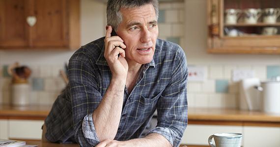 Un hombre de mediana edad está llamando al Programa de Asistencia al Empleado desde su amplia cocina para recibir ayuda con un problema de trabajo