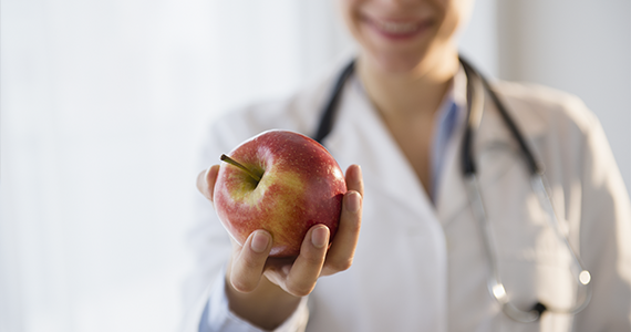 A smiling doctor wearing a white coat and stethoscope offers her patient a fresh apple while they talk comprehensive care