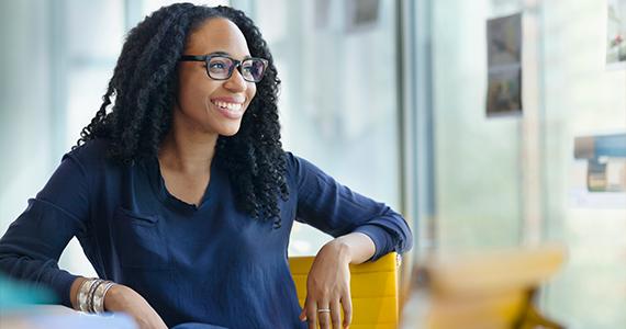 Una joven recién contratada se sienta en una oficina y sonríe a un gerente de RRHH fuera de la pantalla explicando sus nuevos beneficios