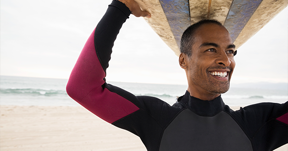 A smiling man is using his paid time off to catch some waves. He is wearing a wetsuit and holds his surfboard over his head