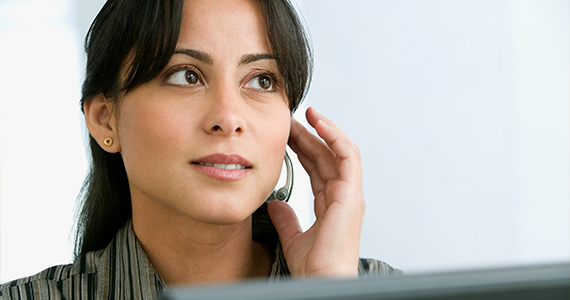 A young woman touches her headset to take a call. She looks ready to answer questions and find solutions