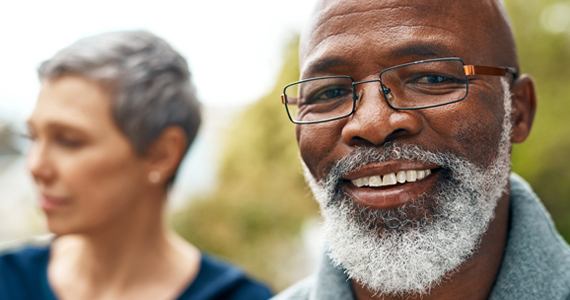A healthy-looking older man smiles feeling secure with his life insurance choices. His partner can be seen in the background
