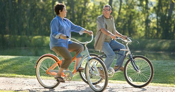 Una pareja de mediana edad charla mientras montan sus bicicletas tranquilamente a lo largo de un camino en un día soleado