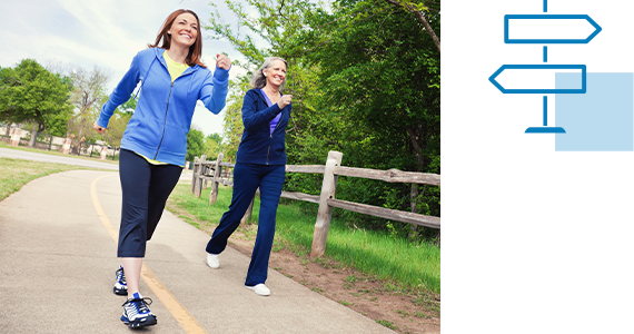 Two middle-aged women are smiling as they power walk down a paved path outside; next to them is a line art signpost