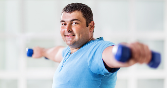 A middle-aged man smiles as he exercises. He holds weights away from his body and has broken a light sweat.