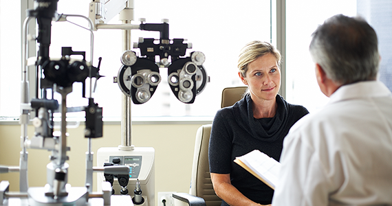 An optometrist consults with his patient in the examination room after completing her vision test