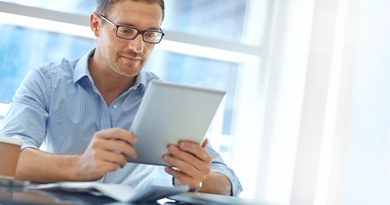A middle-aged man reads about preventative care options on his tablet. He looks relaxed and thoughtful