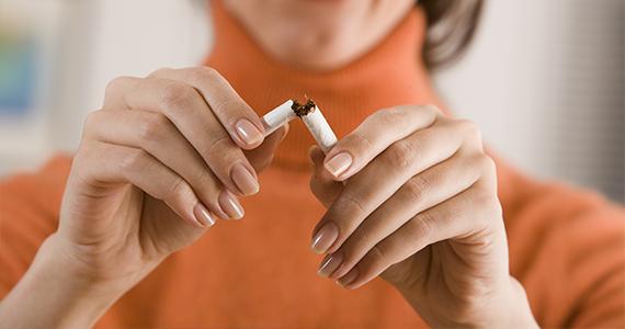 A woman's hands are shown breaking a cigarette in half.